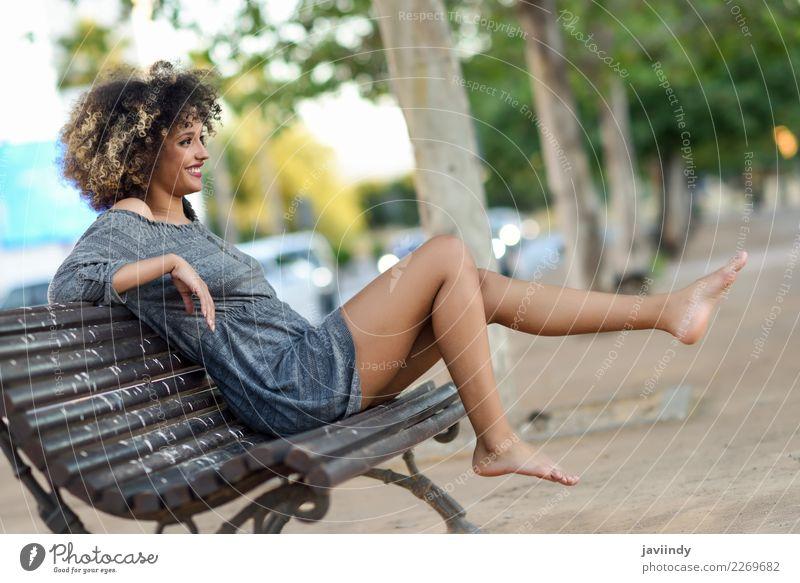 Frau mit Afro-Frisur, die auf einer Bank sitzt und ihre Beine bewegt. Lifestyle Stil Glück schön Haare & Frisuren Gesicht Mensch feminin Junge Frau Jugendliche