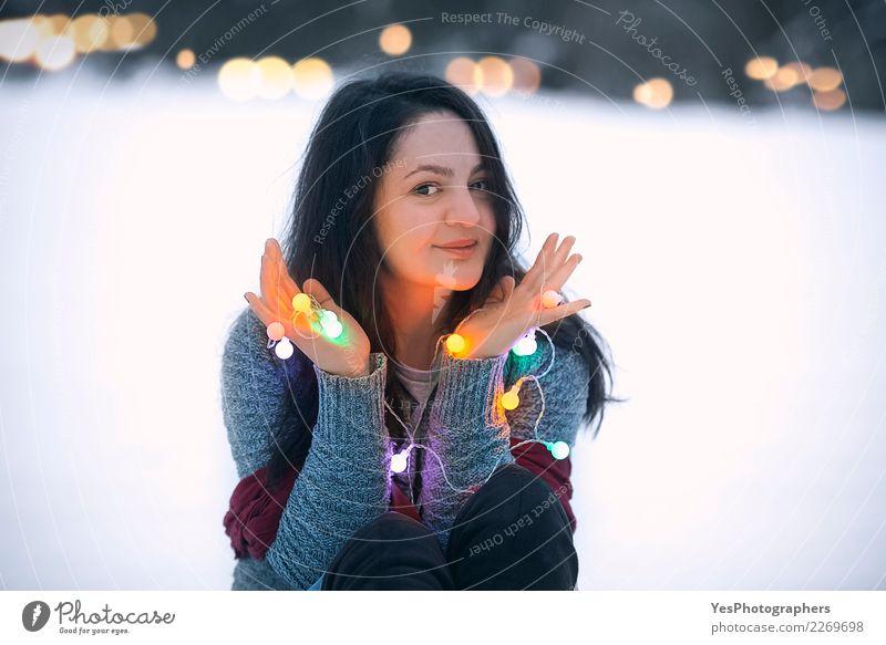Lächelnde Brunettefrau, die Schnur hält, beleuchtet Lifestyle Freude schön Freizeit & Hobby Winter Schnee Dekoration & Verzierung Feste & Feiern