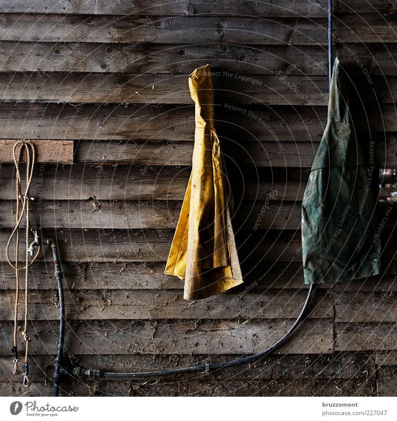 Strickjacken gelb Holz Arbeit & Erwerbstätigkeit dreckig Seil Kunststoff Symbole & Metaphern Bauernhof Landwirt Schlauch Wasserhahn Stall Holzwand gebraucht hängend Arbeitsbekleidung