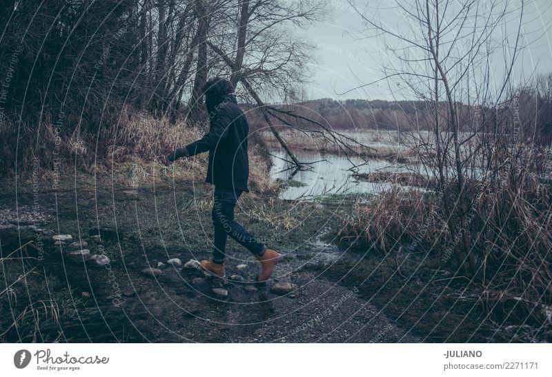 Junger Mann springt auf Felsen, um den Fluss zu kreuzen Mensch Ferien & Urlaub & Reisen Jugendliche Winter Wald Berge u. Gebirge dunkel 18-30 Jahre Erwachsene