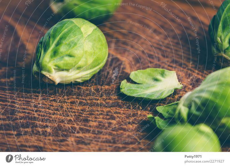 Rosenkohl Lebensmittel Gemüse Bioprodukte Vegetarische Ernährung Diät Schneidebrett Holz frisch braun gelb grün genießen roh Rohkost Farbfoto Nahaufnahme