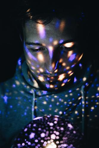 Junger Mann, der von einem Lichtprojektor beleuchtet wird. Stil Design exotisch Mensch maskulin Erwachsene 1 18-30 Jahre Jugendliche Kunst schwarzhaarig