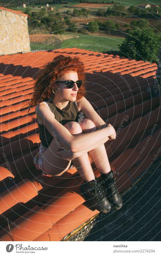 Junge rothaarige Frau, die auf einem Dach sitzt. Lifestyle Stil Haare & Frisuren Wellness Wohlgefühl Sinnesorgane Erholung Ferien & Urlaub & Reisen Tourismus