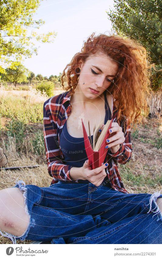 Junge Frau öffnet ein Buch, draußen. Lifestyle schön Sinnesorgane ruhig Freizeit & Hobby lesen lernen Schüler Mensch feminin Jugendliche 1 18-30 Jahre