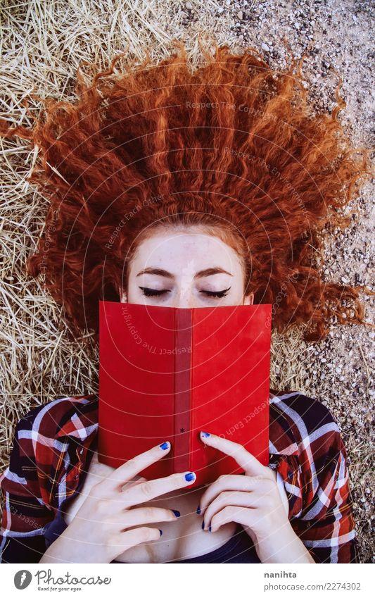 Junge Rothaarigefrau, die ein rotes Buch liest Lifestyle Stil schön Wohlgefühl Sinnesorgane Erholung Freizeit & Hobby lesen Bildung Schüler Mensch feminin