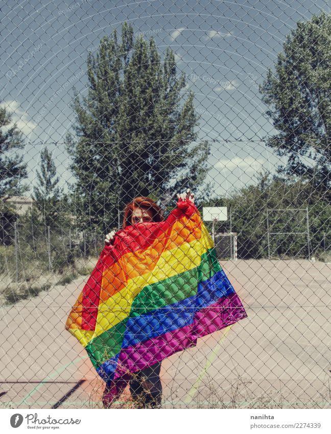 Junge Frau, die eine Regenbogenflagge hinter einem Zaun hält Lifestyle Stil Design Bildung Erwachsenenbildung Schulhof Mensch feminin Homosexualität Jugendliche