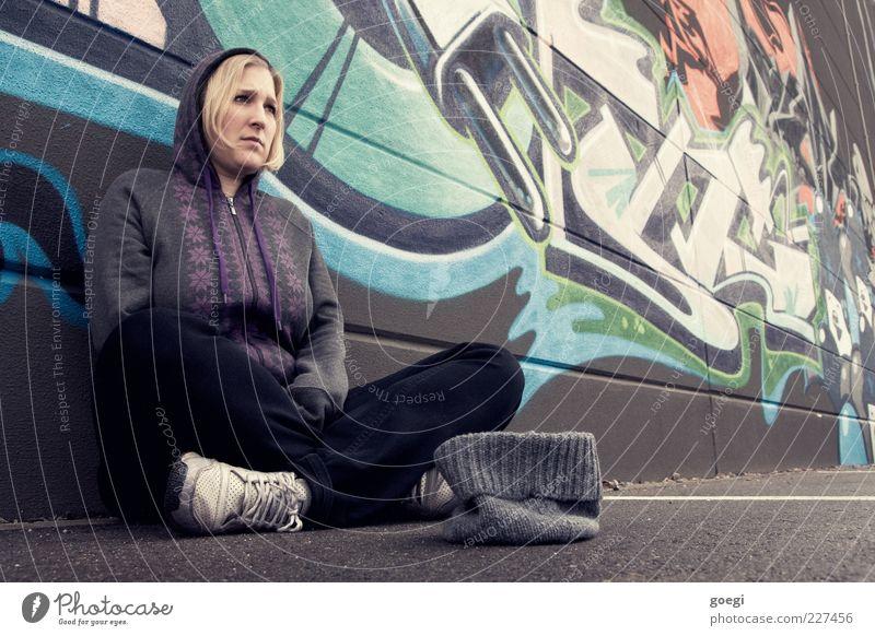 wall street victim Mensch Frau Jugendliche Erwachsene Wand Graffiti Mauer blond Fassade sitzen Armut Schriftzeichen trist 18-30 Jahre Jeanshose Junge Frau