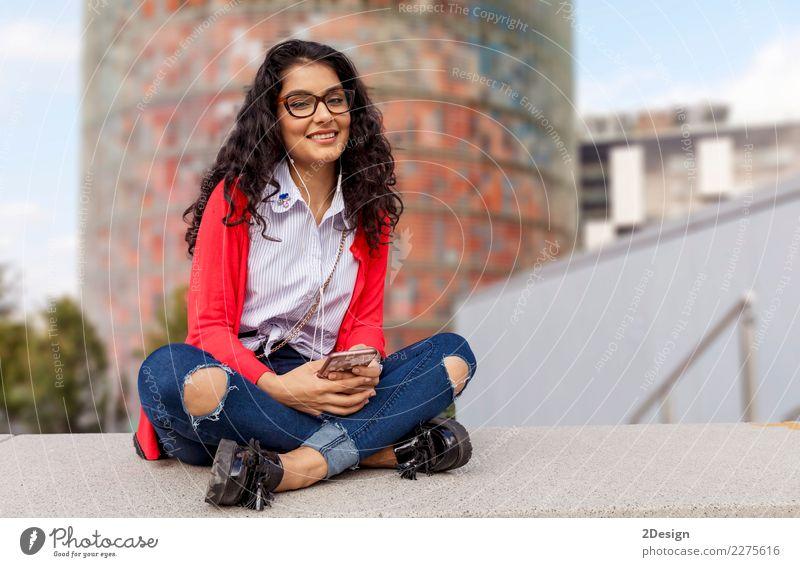 Eine hörende Musik der jungen Frau auf digitalem Tablettensitzen Freude Freiheit Sonne Entertainment Telefon MP3-Player Technik & Technologie Erwachsene