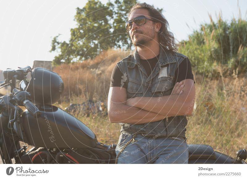 Langhaariger brünetter Typ mit Sonnenbrille, Jeans und Jeanshemd posiert auf einem schwarzen Custom-Motorrad Lifestyle schön Ferien & Urlaub & Reisen Ausflug