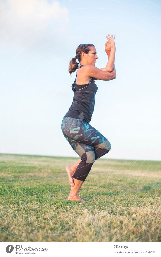 Schönes Mädchen nimmt an Yoga im Park teil Lifestyle harmonisch Erholung Sport Frau Erwachsene Jugendliche Natur Gras sitzen grün Kraft Konzentration