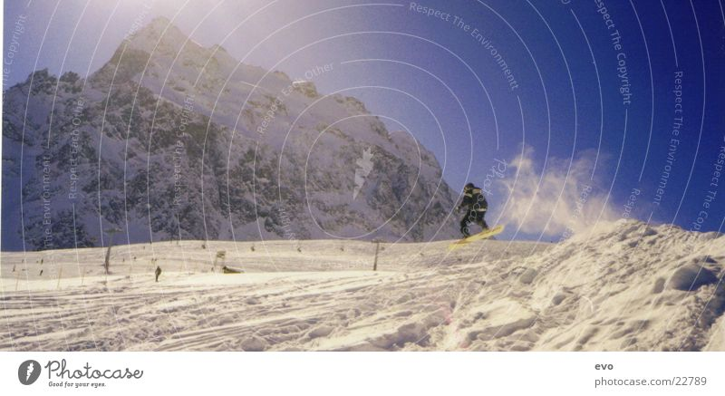 On board Sonne Winter Berge u. Gebirge Schnee Sport springen Alpen Schneebedeckte Gipfel abwärts Schwung Snowboard Freestyle Funsport Skipiste Snowboarding schwungvoll