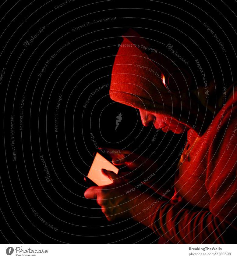 Mann im Hoodie, der Smartphone über schwarzem Hintergrund hält Lifestyle Freizeit & Hobby Spielen Computerspiel Entertainment Musik Handy Bildschirm