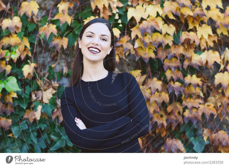 Lächelnde junge Frau mit Herbstblättern. Lifestyle Stil Glück schön Haare & Frisuren Mensch feminin Junge Frau Jugendliche Erwachsene 1 18-30 Jahre Straße Mode