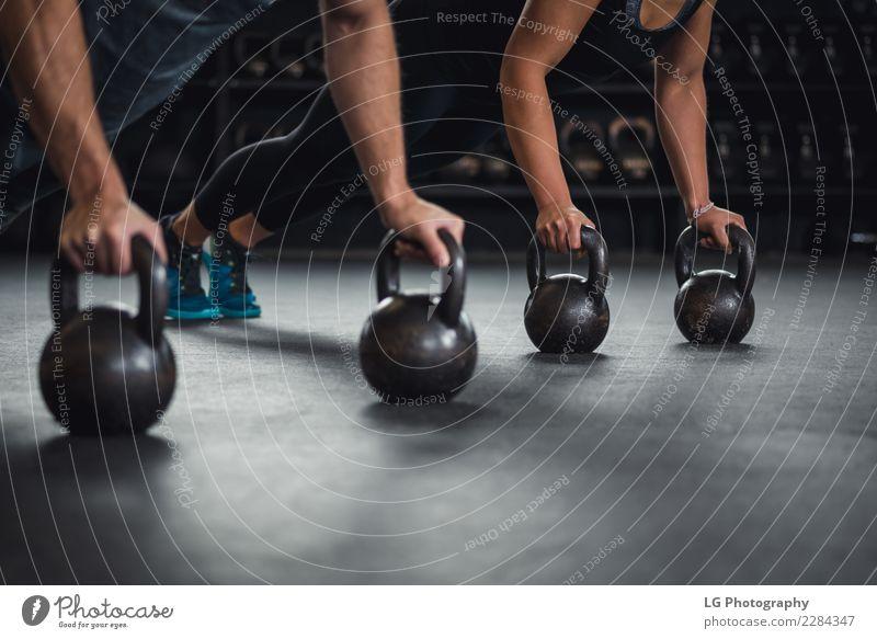 Sportlerin und Sportler, die Liegestütze an zwei Kettlebells machen. Körper Mensch Mann Erwachsene Gebäude Fitness muskulös natürlich stark Kraft Energie