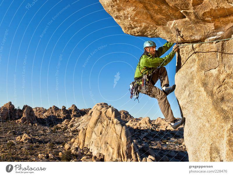 Kletterer, der sich an eine Klippe klammert. Abenteuer Freiheit Berge u. Gebirge Klettern Bergsteigen Erfolg Seil 1 Mensch Natur Landschaft Gipfel hängen