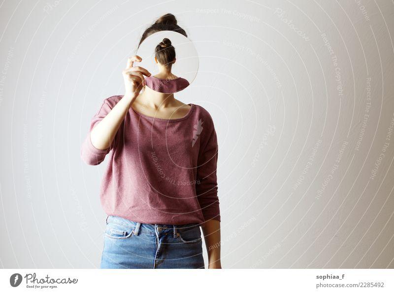 Wer bin ich? Junge Frau, die einen Spiegel vor ihr Gesicht hält. Gesichtslos, Identität nicht erkennbar, der Spiegel zeigt ihren Hinterkopf. Versteckt ihr Gesicht.