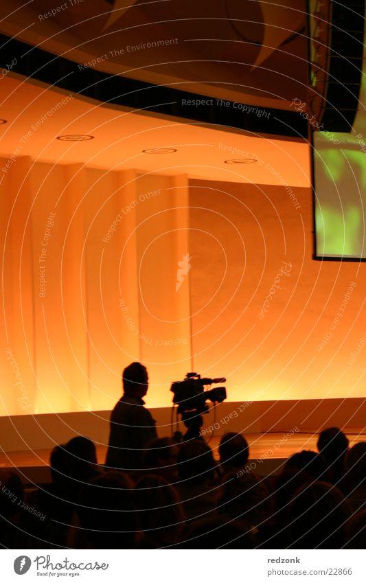 Kameramann Freizeit & Hobby Veranstaltung Publikum Fernseher Videokamera Fotokamera Fernsehen Filmindustrie ästhetisch braun filmen Mitteilung orange Farbfoto
