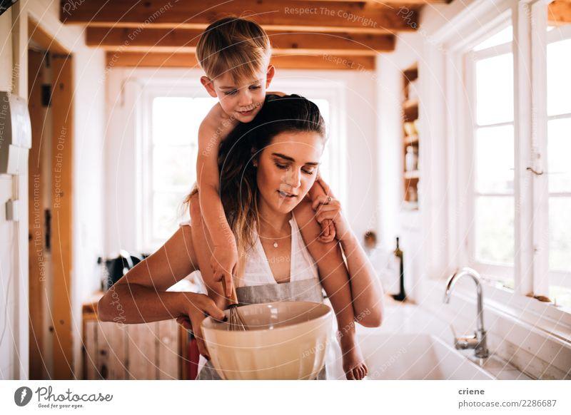 Mutter und Sohn, die zusammen in der Küche backen Winter Kindererziehung Kleinkind Junge Eltern Erwachsene Familie & Verwandtschaft Kindheit Hütte Lächeln