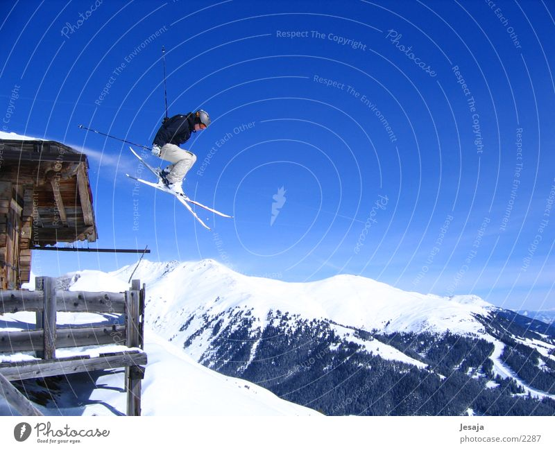 Über die Alpen Himmel weiß blau Winter Ferien & Urlaub & Reisen Sport Schnee springen Berge u. Gebirge Aktion Skifahren gefährlich Fitness Unendlichkeit Hütte sportlich