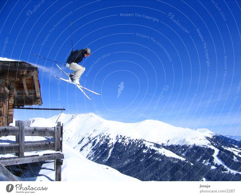 Über die Alpen Himmel weiß blau Winter Ferien & Urlaub & Reisen Sport Schnee springen Berge u. Gebirge Aktion Skifahren gefährlich Fitness Unendlichkeit Hütte