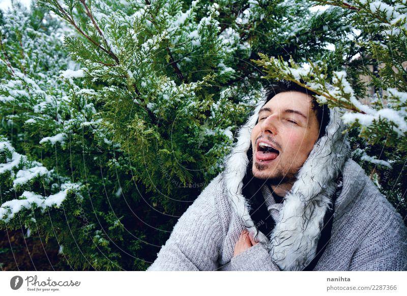 Junger Mann, der den Schnee an einem Wintertag genießt Lifestyle Stil Freude Wellness Leben Wohlgefühl Winterurlaub Mensch maskulin Jugendliche Erwachsene 1