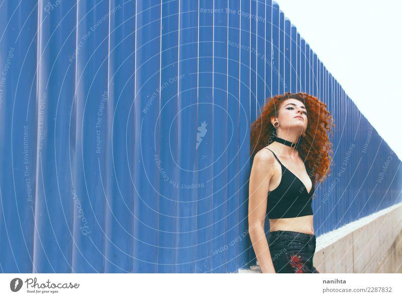 Junge Rothaarigefrau, die an einer blauen Wand sich lehnt Lifestyle elegant Stil schön Körper Haare & Frisuren Wellness Sinnesorgane Erholung Mensch feminin