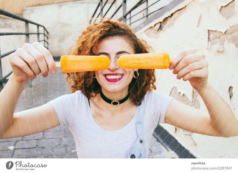 Junge glückliche Frau, die zwei orange Eiscreme anhält Mensch Ferien & Urlaub & Reisen Jugendliche Junge Frau Sommer Stadt schön Freude 18-30 Jahre Erwachsene