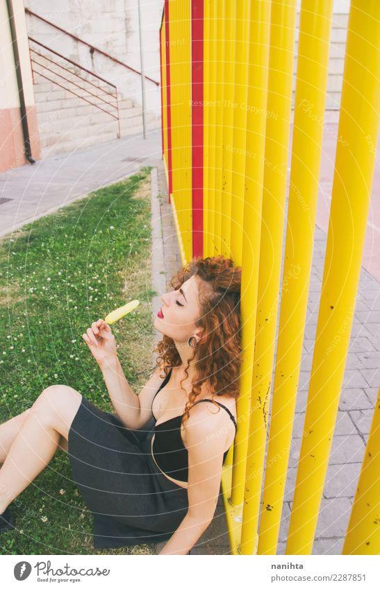Junge Frau in einem Park, der eine ZitronenEiscreme genießt Mensch Jugendliche Sommer Erholung Freude 18-30 Jahre Erwachsene Essen Leben Lifestyle feminin Stil