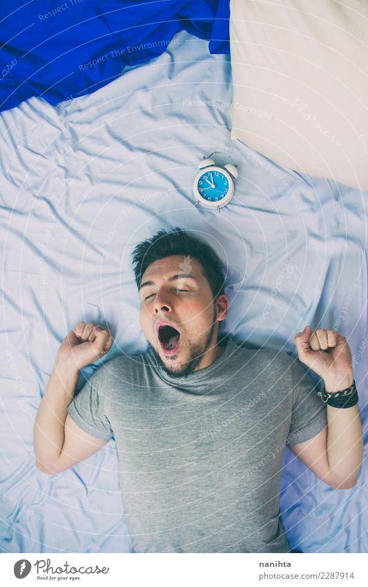 Junger Mann, der in seinem Bett gähnt Mensch Jugendliche blau Erholung Erwachsene Lifestyle Gesundheit Zeit Stimmung Arbeit & Erwerbstätigkeit Uhr maskulin