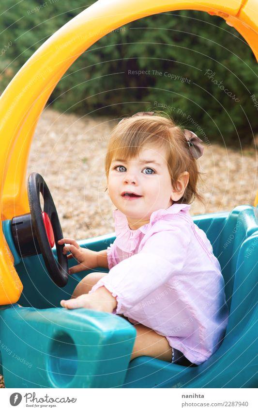 Glückliches kleines Mädchen spielt mit einem Spielzeugauto. Lifestyle Freude Wellness Wohlgefühl Spielen Kinderspiel Kindererziehung Schulhof Mensch feminin