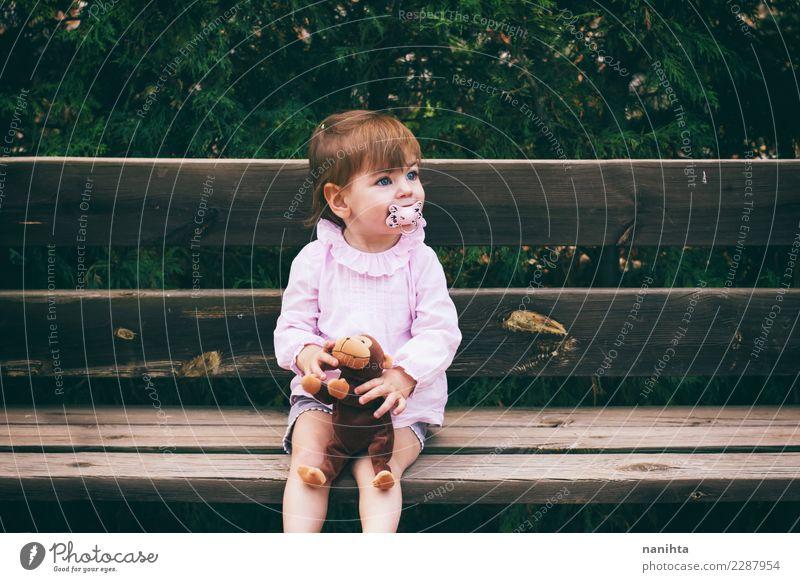 Reizendes kleines Mädchen, das in einer Holzbank sitzt Mensch Natur schön Erholung Freude Lifestyle Umwelt feminin Freizeit & Hobby Park Kindheit sitzen