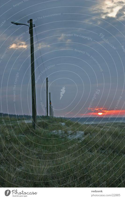 Dünen im Abendrot III Sonne Meer Wolken dunkel Wiese Gras Stein Beleuchtung Hügel Zaun Stranddüne Strommast