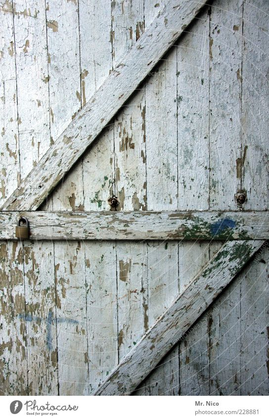 der lack ist ab Hütte Ruine Bauwerk Tür alt dreckig kaputt Holztür Lagerschuppen Scheunentor weiß abblättern verfallen antik Holzbrett Maserung Vergänglichkeit