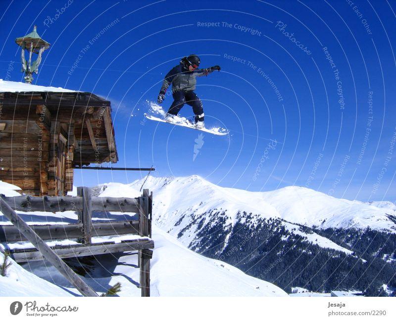 Snowboardsprung springen hoch groß Dach Schneebedeckte Gipfel Hütte Mut Terrasse abwärts Schneelandschaft Blauer Himmel Snowboard Freestyle Zillertal Snowboarding Holzhütte