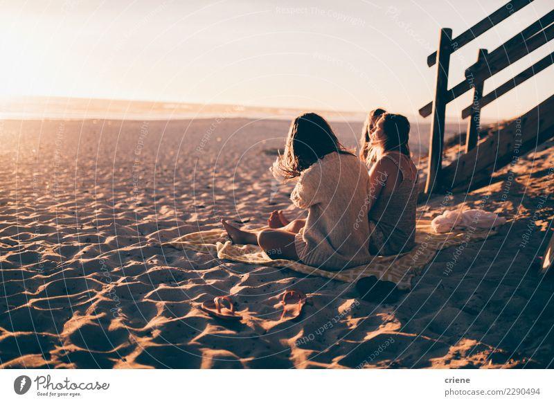 Gruppe Freunde, die auf dem Strand sitzen und Sonnenuntergang genießen Glück Erholung Freizeit & Hobby Ferien & Urlaub & Reisen Party feminin Freundschaft