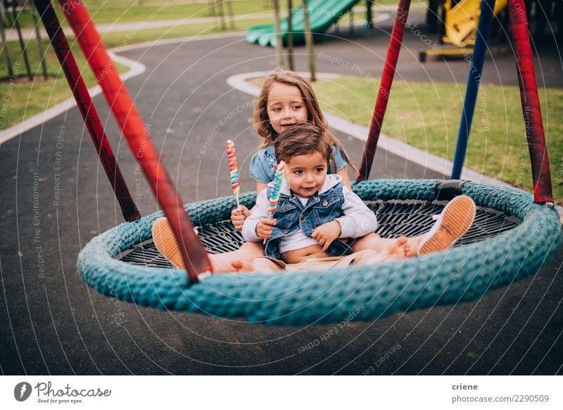 Nette junge sublings, die zusammen auf Schwingen sitzen Freude Glück Spielen Kleinkind Schwester Familie & Verwandtschaft Park Spielplatz Lächeln Umarmen