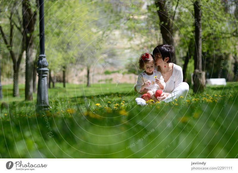 Mutter, die ihre kleine Tochter im Stadtpark küsst Kind Frau Mensch Blume Freude Erwachsene Lifestyle Liebe Gefühle feminin Gras Familie & Verwandtschaft Paar