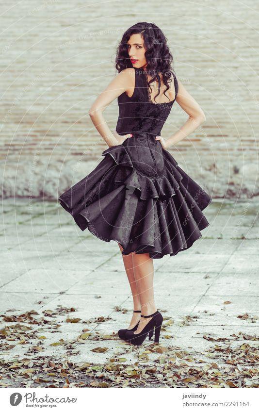Frau, die schwarzes Kleid mit dem gewellten Haar trägt. Spanischer Stil elegant schön Haare & Frisuren Haut Gesicht Mensch feminin Junge Frau Jugendliche