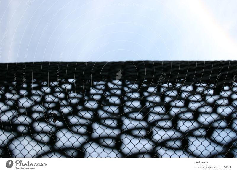 Freiheitszaun I Zaun Gitter Maschendraht Pferch Barriere schwarz Dinge Blick Himmel Netz Justizvollzugsanstalt blau Perspektive