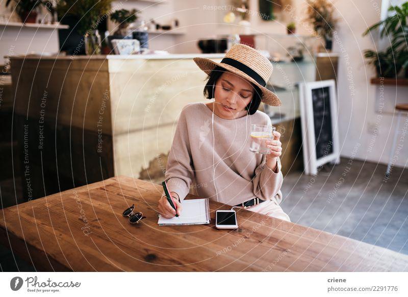 Asiatische Schreibensanmerkungen der jungen Frau im Notizbuch trinken Tisch Musik Arbeit & Erwerbstätigkeit Erwachsene Jugendliche Musiknoten Hut Papier