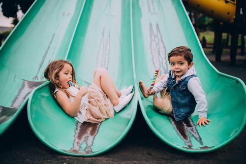 Nette kaukasische Geschwister, die auf Dia auf Spielplatz sitzen Essen Freude Glück Junge Schwester Familie & Verwandtschaft Kindheit Lächeln niedlich Bruder