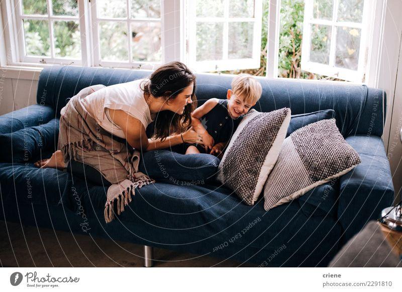 Glückliche Mutter und Kleinkind, die zu Hause auf Couch streichelt Kindererziehung Erwachsene Familie & Verwandtschaft Kindheit genießen Lächeln lachen