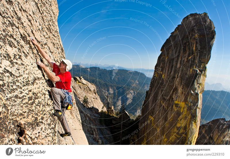 Männlicher Kletterer, der sich an eine steile Klippe klammert. 1 Mensch 30-45 Jahre Erwachsene sportlich Tapferkeit selbstbewußt Kraft Willensstärke Mut