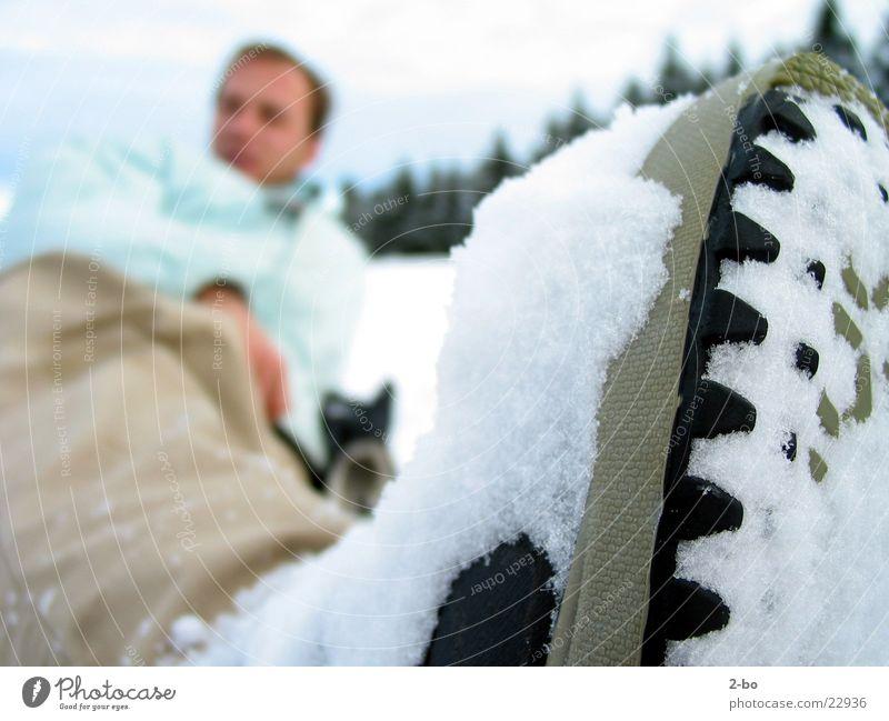 Ein Tag im Schnee Mann Schnee liegen anonym rau Gummi Winterurlaub Noppe winterfest Snowboarder Wintertag Schuhsohle Winterbekleidung Wintersportbekleidung