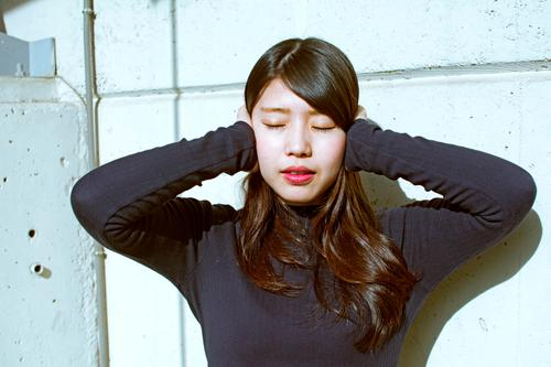 Portrait von Soan Frau Lifestyle exotisch schön Gesicht Mensch feminin Junge Frau Jugendliche Mauer Wand Mode berühren hören gefährlich Nervosität Neid betrügen
