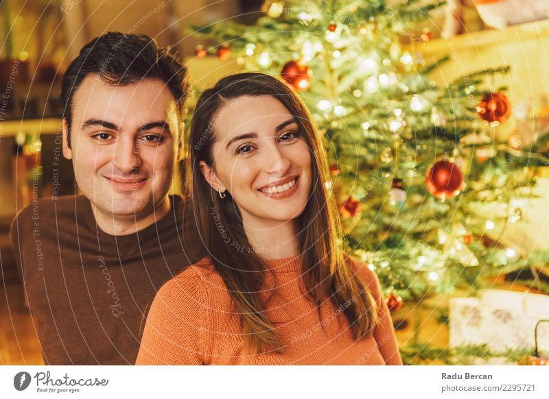 Glückliches Paar Portrait und Weihnachtsbaum Frau Mensch Jugendliche Mann Weihnachten & Advent Junge Frau Farbe schön grün Junger Mann Baum rot Erholung Haus