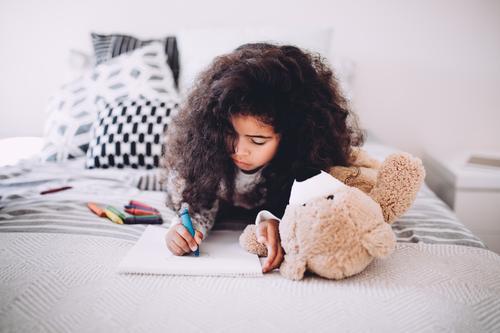 Afroamerikanisches kleines Mädchen beim Zeichnen mit Buntstiften Freude Glück schön Kind Schule Frau Erwachsene Kindheit Papier Lächeln träumen Fröhlichkeit