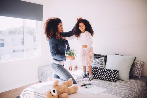 Junge Mutter, die mit kleiner Tochter spielt Freude Glück schön Spielen Haus Schlafzimmer Kindererziehung Eltern Erwachsene Familie & Verwandtschaft lachen