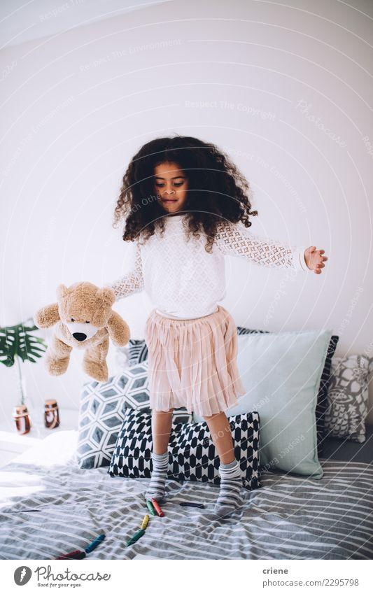 Kleines afrikanisches Mädchen, das auf Bett mit Teddybären springt Freude Glück schön Spielen Kind Mensch Kindheit Spielzeug lachen springen Fröhlichkeit klein