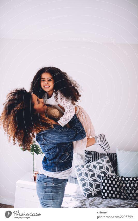 Eine Mutter, die ihre kleine Tochter hält und schwingt. Freude Glück schön Spielen Haus Schlafzimmer Kindererziehung Eltern Erwachsene Familie & Verwandtschaft